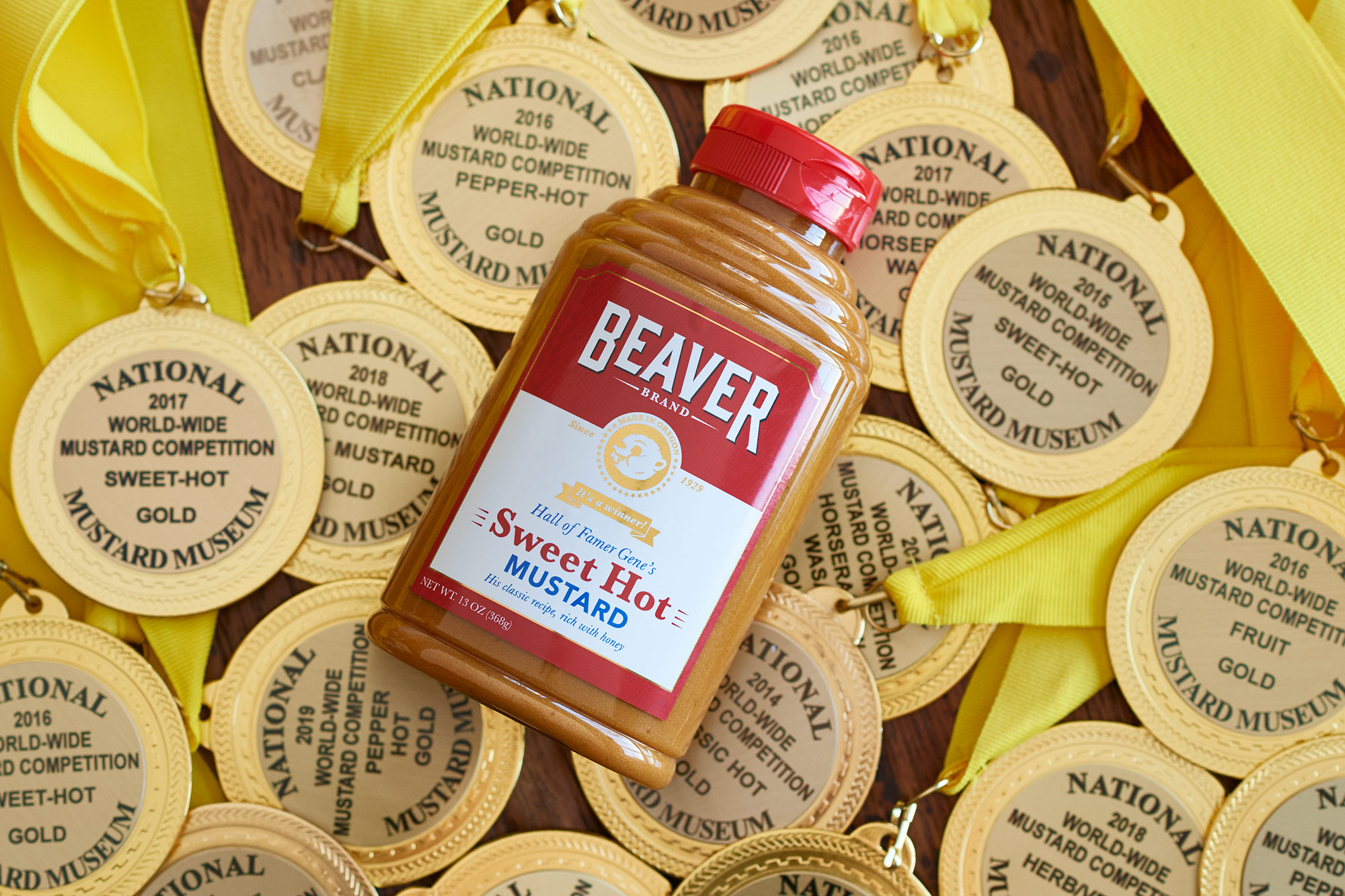 Beaver Brand Sweet Hot Mustard bottle laying on a table full of World-Wide Mustard Competition gold medals